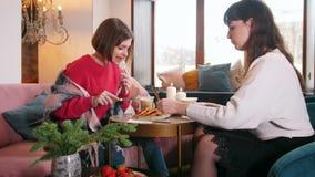 Dwa młodych kobiet obsiadanie w kawiarni i opowiadać podczas gdy jedzący blin zbiory