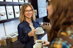 Dwa młodych kobiet piękny pić kawowy i opowiadać w sklep z kawą zdjęcia stock