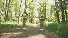 Dwa młodych kobiet skokowa arkana w parku w zwolnionym tempie pojęcie zdrowego stylu życia zbiory