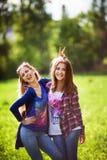 Dwa młodych kobiet uściśnięcie i śmiać się przy parkiem Obrazy Royalty Free