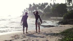 Dwa młodzi ludzie chodzą z surfboard na plaży przy zmierzchu czasem zbiory wideo