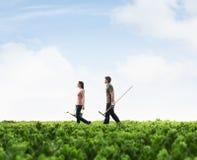 Dwa młodzi ludzie niesie ogrodnictwa wyposażenie chodzi przez zielenieją pole z roślinami Zdjęcie Stock