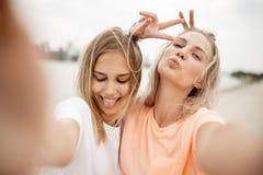Dwa m?odej ?adnej blondynki dziewczyny bior? selfie na pla?y na ciep?ym wietrznym dniu fotografia stock