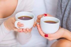 Dwa młodej damy trzyma teacups Zdjęcie Royalty Free