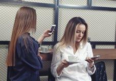 Dwa młodej dziewczyny patrzeje ich smartphones z absorbedly przy kontuarem w kawiarni Obraz Royalty Free