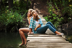 Dwa młodej dziewczyny siedzi na drewnianym moscie Fotografia Stock