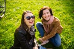 Dwa młodej kobiety odpoczynek na zielonym gazonie Zdjęcie Royalty Free