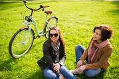 Dwa młodej kobiety odpoczynek na zielonym gazonie Obrazy Royalty Free