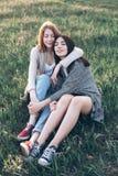 Dwa młodej kobiety siedzi na trawie Obrazy Stock
