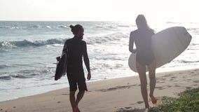 Dwa m?odzi ludzie chodz? z surfboard na pla?y przy zmierzchu czasem zbiory wideo