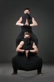 Dwa męskiego tancerza pozuje w ninja kostiumach na zmroku - szary backgroun Zdjęcie Stock
