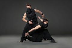 Dwa męskiego tancerza pozuje w ninja kostiumach na zmroku - szary backgroun Obraz Stock