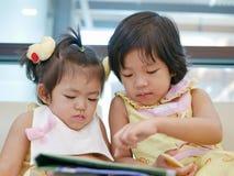 Dwa mała Azjatycka dziewczynka, siostry, obsiadanie i dopatrywanie, smartphone wpólnie, podczas gdy czekać na jej matki zdjęcia royalty free