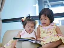 Dwa mała Azjatycka dziewczynka, siostry, obsiadanie i dopatrywanie, smartphone wpólnie, podczas gdy czekać na jej matki fotografia royalty free
