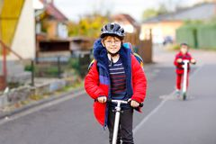 Dwa małe dziecko chłopiec jedzie na pchnięcie hulajnoga na sposobie do lub z szkoły Ucznie jedzie przez deszczu 7 rok fotografia royalty free