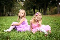 Dwa mała śliczna dziewczyna w pięknych sukniach jest roześmiana w sumie Fotografia Stock