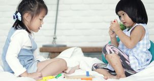 Dwa mała azjatykcia śliczna dziewczyna bawić się colourful drewnianego blok na łóżku wpólnie zdjęcie wideo
