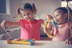 Dwa mała dziewczynka przy muzyczną szkołą hełmofonu czarny zamknięty wizerunek odizolowywał mikrofonu ochraniacza miękką część w  Obrazy Royalty Free