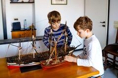 Dwa małe dziecko chłopiec bawić się z żeglowanie statku modelem indoors Z podnieceniem dzieci, rodzeństwa i najlepszy przyjaciele obrazy stock