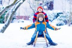 Dwa małe dziecko chłopiec cieszy się sanie przejażdżkę w zimie Fotografia Stock