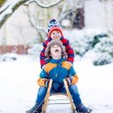 Dwa małe dziecko chłopiec cieszy się sanie przejażdżkę w zimie Obraz Royalty Free