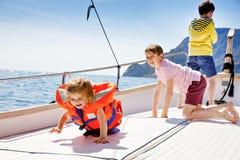 Dwa małe dziecko chłopiec i berbeć dziewczyna cieszy się żeglowanie łódź one potykają się Rodzinni wakacje na oceanie lub morzu n fotografia stock