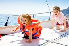 Dwa małe dziecko chłopiec i berbeć dziewczyna cieszy się żeglowanie łódź one potykają się Rodzinni wakacje na oceanie lub morzu n zdjęcia stock