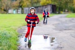 Dwa małe dziecko chłopiec jedzie na pchnięcie hulajnoga na sposobie do lub z szkoły Ucznie jedzie przez deszczu 7 rok zdjęcia stock
