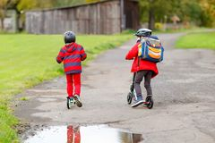 Dwa małe dziecko chłopiec jedzie na pchnięcie hulajnoga na sposobie do lub z szkoły Ucznie jedzie przez deszczu 7 rok zdjęcie stock