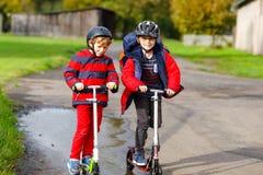 Dwa małe dziecko chłopiec jedzie na pchnięcie hulajnoga na sposobie do lub z szkoły Ucznie jedzie przez deszczu 7 rok fotografia stock