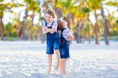 Dwa małe dziecko chłopiec ma zabawę na tropikalnej plaży obrazy stock