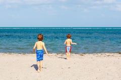 Dwa małe dziecko chłopiec ma zabawę na tropikalnej plaży zdjęcie royalty free
