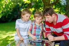 Dwa małe dziecko chłopiec, ojciec bawić się wpólnie warcabów gemowych i fotografia royalty free