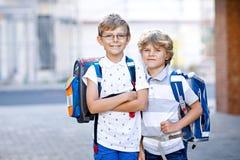 Dwa małe dziecko chłopiec z plecakiem lub satchel Schoolkids na sposobie szkoła Zdrowi uroczy dzieci, bracia i zdjęcia stock