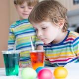 Dwa małego blondynu żartują chłopiec barwi jajka dla wielkanocy Fotografia Royalty Free