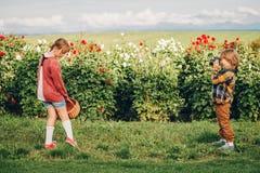 Dwa małego dziecka bawić się wpólnie outside w kwiatu ogródzie Obrazy Royalty Free