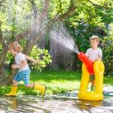 Dwa małego dziecka bawić się z ogrodowym wężem elastycznym i wodą w lecie zdjęcie royalty free