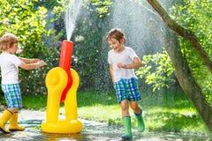 Dwa małego dziecka bawić się z ogrodowym wężem elastycznym w lecie obraz stock
