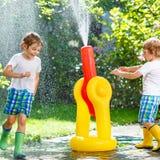Dwa małego dziecka bawić się z ogrodowym wężem elastycznym w lecie zdjęcia royalty free