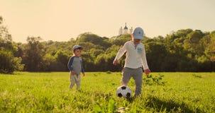 Dwa małego dziecka bawić się z piłki nożnej piłką roześmianą i ono uśmiecha się przy zmierzchem zbiory wideo