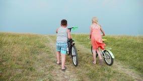 Dwa małego dziecka - chłopiec i dziewczyna jesteśmy napędowymi bicyklami w górę wzgórza, błyskawica błyski w odległości przeciw j zbiory wideo