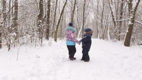 Dwa małego dziecka chodzi w zimie w parku zdjęcie wideo
