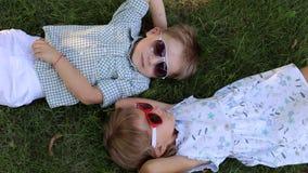 Dwa małego dziecka kłama na trawie konfrontacyjnej w okularach przeciwsłonecznych zbiory wideo