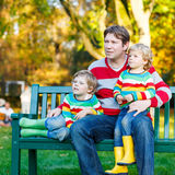 Dwa małego dziecka potomstwa i chłopiec ojcują obsiadanie wpólnie, jesień, o Obraz Royalty Free
