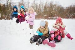 Dwa małego dziecka siedzą na śniegu i innym trzy stojaku na boku zdjęcia royalty free