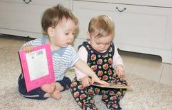Dwa małego dziecka siedzą na podłoga i czytają książki Dziewczyna i chłopiec obraz royalty free