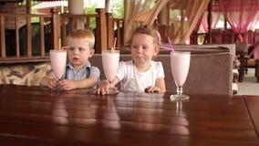 Dwa małego dziecka siedzi w kawiarni z milkshakes zbiory