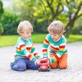 Dwa małego przyjaciela bawić się z czerwonym autobusem szkolnym Zdjęcia Royalty Free