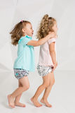 Dwa małej śmiesznej i roześmianych dziewczyny w identycznych ubraniach różni kolory bawić się w białym studiu Zdjęcie Royalty Free