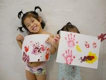 Dwa małej Azjatyckiej dziewczynki, siostry, cieszyli się pokazywać ich grafika po robić one samodzielnie - dzieci handprints obrazy stock